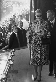 Another lovely lady in leopard! Princess Grace and Prince Rainier at a football match, photographed by Eve Arnold, 1962.