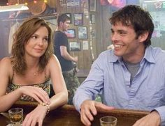 "27 Dresses (2008). It's the ""spontaneous"" moment when Kevin (James Marsden) and Jane (Katherine Heigel) broke into a rousing rendition of ""Bennie and the Jets."""