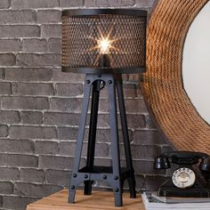 Add industrial-chic style to your living room or entryway with this handsome lamp, crafted of riveted metal and showcasing a metal mesh shade. ...