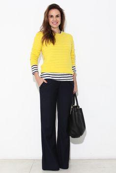 look de trabalho moderno e elegante: pantalona de alfaiataria preta, t-shirt listrada e sobreposição de malha amarela.