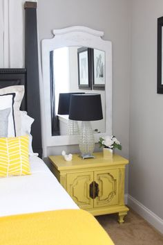 Black gray and yellow master bedroom decor. Love the mirror above the nightstand&;the lamp is a li&; Black gray and yellow master bedroom decor. Love the mirror above the nightstand&;the lamp is a li&; Yellow Side Table, White Side Tables, Yellow Master Bedroom, Bedroom Black, Yellow Nightstand, Yellow Dresser, Nightstand Lamp, Dresser Mirror, Bedside Tables
