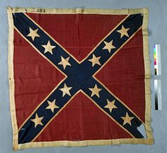 "First Texas Infantry Regiment  This oversized Confederate battle flag with the St. Andrew's cross design is another rare variant. Except for its size, it conforms to the ""Fourth Bunting Issue"" of the flag with 13 stars. The center star on this flag is missing."