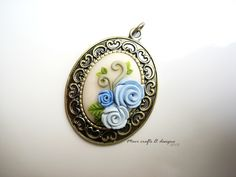 light blue polymer clay roses in an antiqued brass oval setting