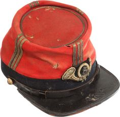 "Colorful New York Zouave Officer's Kepi.New York Zouave Officer's Kepi Among the Civil War's most colorful items of headgear. This kepi ranks with the best. The scarlet body is sewn to a 1 ½"" tall blue band. Three ¼"" wide strips of gold lace rise up the front, back and sides of the scarlet cloth to the crown, which is edged with a single, narrower strip of gold lace. . The ½"" glazed leather chin strap is affixed by two State of N. Y. ""Excelsior"" buttons."