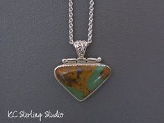 This hand-smithed necklace is made with natural native Royston turquoise from Nevada. The stone has beautiful green turquoise in a tan matrix.  This pendant was totally handmade by me out of fine and sterling silver. The pendant on this necklace is 1.5 inches (35mm) long including the decorative bail. The stone measures 23mm x 35mm. It hangs on a sterling silver chain that is 16 inches long with a 2-inch extender. The chain is finished with a handmade clasp and tiny sterling heart charm. All…