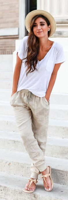 Beachy chic: cozy white tee, neutral linen pants, thong sandals, Panama hat.
