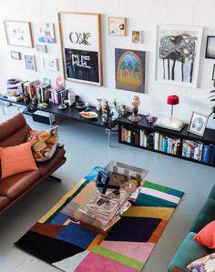 sala de estar decorada com tapete colorido, decoração moderna, muitos quadros na parede, sofá de couro marrom com almofada laranja, livros e revistas na decoração