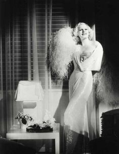 Jean Harlow in a glamorous boudoir set (looks like a slip beneath the robe) with some seriously feather-y goodness going on around those sleeves.