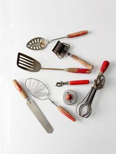 circa 1930s - 1940s A gorgeous collection of vintage Americana kitchen utensils. This is an 8 piece collection that feature red wood handles. An amazing patina colors and tones the pieces. - 8 piece c