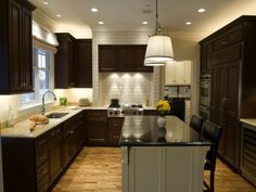 The off-white brick and cream wall accents in this transitional U-shaped kitchen serve to showcase the dark walnut cabinets & dark island countertop.