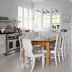 love the assorted white chairs around a farmhouse table in this cottage-style kitchen