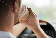 stock photo of transportation and vehicle concept man drinking coffee while driving the car
