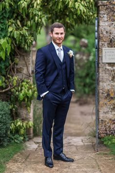 Groom wears a three piece navy bespoke suit made by Dress 2 Kill in Waterloo -  Image by  Ann-Kathrin Koch Photography - A wedding at Barnsley House with the bride in Suzanne Neville. A peony bouquet and white and blush colour theme. Mercury votive table decorations and white pom poms. Photography by Ann-Kathrin Koch.