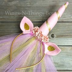 GOLD AND PINK UNICORN CROWN HEADBAND w/ gold and pink tulle veil This beautiful handmade headband is adorned with a crown of mauve pink silk flowers and rhinestones. The ears are made of felt and are curved to add dimension. The felt unicorn horn is hand sewn and an amazing 6 tall, and wrapped with beautiful silk ribbon. A beautiful glitter gold and pink 14 Tulle Veil flows down the back. A great costume accessory for a girls birthday party, flower girl, hen party, bachelorette bride to...