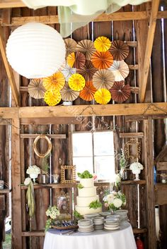 paper laterns & fan board over cake table, framed by empty antique frames