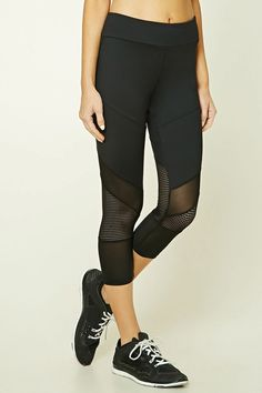 6ff89b5806e93 A pair of stretch-knit athletic capri leggings featuring sheer and  open-mesh panels