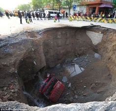 Plummet: A lorry lies at the bottom of a huge sinkhole on Shiliuzhuang road, in Beijing, China in April last year. The driver and his passenger jumped out of the vehicle before it sank into the hole.