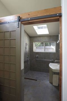 This special-needs bathroom features salvaged beams, a sliding door with barn hardware and a shower large enough for someone in a wheelchair--or two muddy grandchildren.Click To Enlarge
