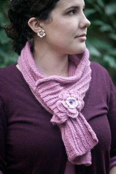 Pink knitted scarf with floral embellishment