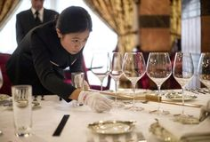 A butler in training inspects the precise distance between cutlery on a table.