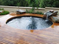 Cool Design Ideas with Varnished Wooden Deck Round Shape Green Plant and Grass Cute Small Waterfall Amazing Stone and Style of Fence for Outdoor Pool | 21 Attractive Wooden Deck Design of Swimming Pool