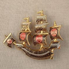 This style of jewelry is called Damascene; more to read about it here http://en.wikipedia.org/wiki/Damascening This one is Vintage PIRATE Ship Spanish TOLEDO Damascene Enamel Signed SPAIN c.1960's