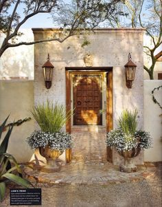 French urns flank entry to Spanish-style courtyard;