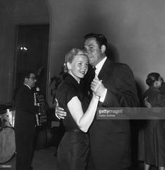 1955: American actor and singer Doris Day dancing with her third husband, agent Marty Melcher, at a party. A musician plays the accordion in the background.