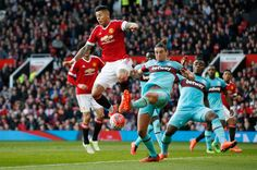 Andy Carroll in action with Marcos Rojo