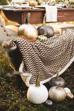 gold besprühte Kürbisse als moderne Herbstdeko im Garten