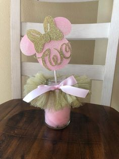 This beautiful pink and gold Minnie Mouse inspired Centerpiece, is attached to a high quality paper straw, it can be used as a cake topper or as a centerpiece. This listing includes: 1 tutu 1 Minnies shape with age CAN BE MADE FOR ANY AGE. All high quali Theme Mickey, Minnie Mouse Birthday Decorations, Minnie Mouse Theme Party, Minnie Mouse First Birthday, Minnie Mouse Baby Shower, Minnie Mouse Favors, Minnie Mouse Cake Topper, Mickey Birthday, Minnie Mouse Rosa