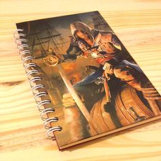 8.5 x 5.5 hard cover journal twin loop bound  Cover and back are made with thick sturdy chipboard.  Cover is wrapped with recycled Assassins Creed picture.