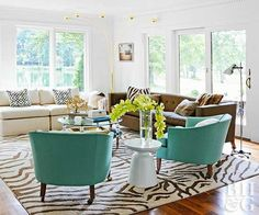 A room wrapped in white is the perfect foundation for a two-neutral mix, plus a dose of color. In this living room, cream and brown introduce variation to the neutral side of the color palette, which is tied together by the abstract zebra print rug. Dusty aqua club chairs really stand out in the light-filled and neutral space.
