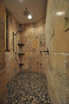 I love the stone and pebble flooring in this shower. It is a wonderful natural look. But I would want recessed shelving in the wall. I like the hand wand on the the slider bar, too.  I love it!