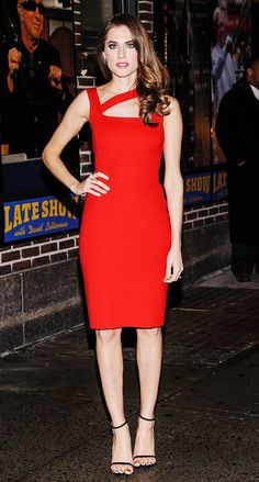 Allison Williams in a red dress and ankle strap high heels