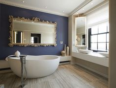 Another gorgeous bathroom - look at that mirror and how it contrasts with the blue wall!