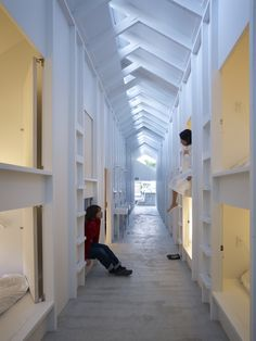 A forest of white slim wooden pillars organizes indoor spaces in Koyasan Guesthouse