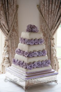 Tiered ivory wedding cake with purple flower detail