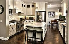 Love the off-white cabinets and dark wood flooring in this kitchen