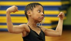 Hannah Clemons, 6, strains as she flexes her muscles during ballet class at Rainey Institute. Clemons is one of eight students in the class taught by Groundworks DanceTheatre's Noelle Cotler. (Gus Chan / The Plain Dealer)