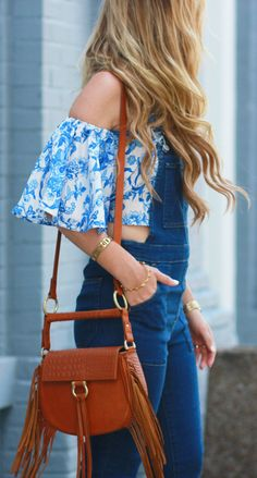 Flared overalls styled with a floral off the shoulder top, fringe Sancia bag, and round Ray Bans for a bohemian inspired summer outfit