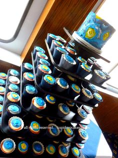 "Van Gogh Starry Night Wedding Cupcakes by Cupid Cupcakery. The bride asked for an interpretation of Van Gogh's famous painting, ""Starry Night"" on both her little cake and each wedding cupcake. I'm no Van Gogh, but painted my own interpretation using royal icing.    A bit hard to get a picture as this was on the Nautica Queen river boat and quarters were pretty tight."