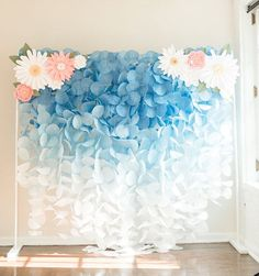 ***This backdrop does NOT include the paper flower pieces.** This gorgeous blue ombre paper garland backdrop would be a stunning accent for birthdays, weddings, or any other special occasion. This airy garland captures light beautifully to create a whimsical backdrop for any event. The displays features a beautiful reverse ombre fading from dark, medium, and light cornflower blue into white. Each coffee filter is hand-dyed to create the bright and bold colors. This v shaped display measures…