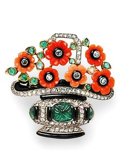 Art Deco Carved Emerald and Coral Purse Clasp, France, designed as a flower basket with carved coral flowerheads, old single-cut diamond centers, and cabochon emeralds, the basket centering a carved emerald, and set throughout with rose-cut diamonds, black enamel accents, platinum-topped 18kt gold mount, guarantee stamps, 1 1/4 x 1 1/2 in., joined to a brass plate for purse attachment.
