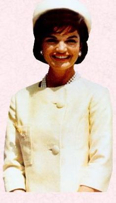 Jackie Kennedy wearing a light colored suit with matching hat and her three strand pearl necklace