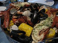The New England clam bake is a traditional method of cooking shellfish seafood, such as lobster, mussels, crabs, soft-shell clam, and quahog.[1] The food is traditionally cooked by steaming the ingredients over layers of seaweed. The shellfish can be supplemented with vegetables, such as onions, carrots, and corn on the cob.