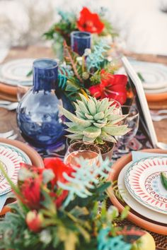 Table idea: bright flowers mixed with succulents and bright vases. Jewel tones + dark blue.