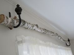 birch tree curtain rod, hung it using the tie-back curtain hardware!  clever girl.