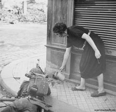 A civilian woman pours a drink of cider for a Bren gunner in action in Lisieux, 22 August 1944 / Imperial War Museum