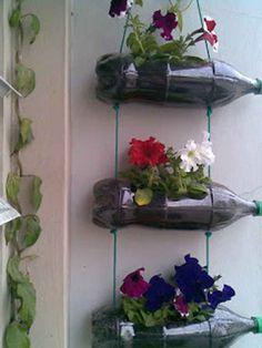 <p>Uma floreira reciclada feita com garrafas de plastico e fio de nylon, é muito facil de fazer e vai enfeitar a sua varanda. É só fazer um corte rectangular na lateral das garrafas, furar com um espeto ou prego aquecido de forma a ter um furo em baixo e outro …</p> Plastic Bottle Planter, Reuse Plastic Bottles, Plastic Bottle Crafts, Hanging Plant Wall, Hanging Pots, Diy Hanging, Vertical Garden Design, Backyard Garden Design, Garden Crafts